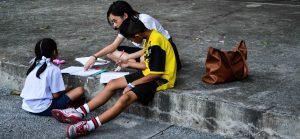 Bangkok in Thailandia. Ragazza insegna ai bambini per strada