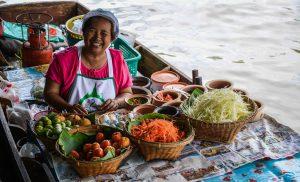 Donna vende frutta sulla barca nel mercato galleggiante di Bangkok in Thailandia