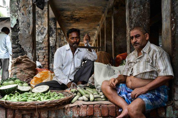 Due uomini vendono ortaggi al mercato di Varanasi in India