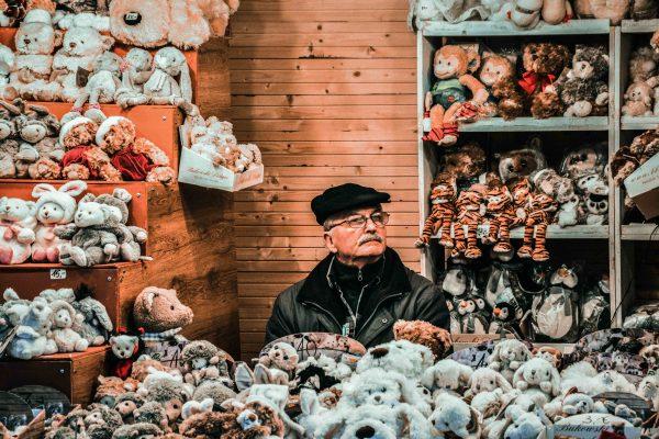 Vienna, Austria. Uomo immerso nella sua casetta di pupazzi in vendita