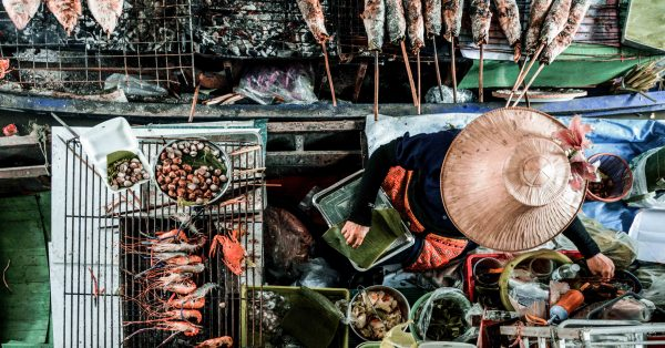 Donna lavora sulla barca nel mercato galleggiante di Bangkok in Thailandia
