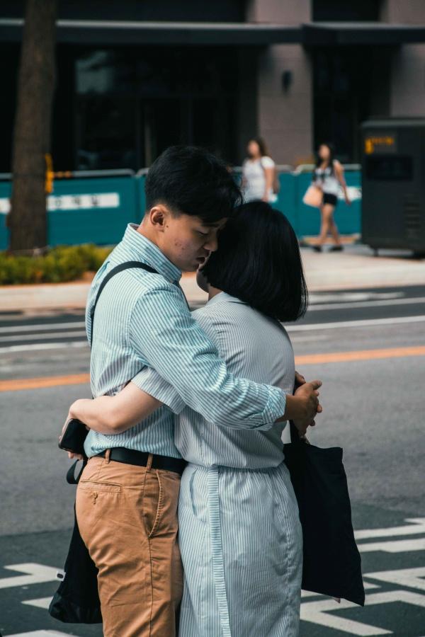 Ragazzo e ragazza si abbracciano per strada a Seoul, Corea del Sud