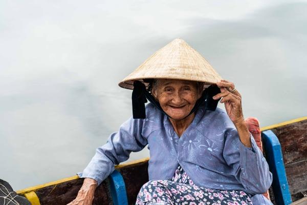 Signora sorridente nel canale di Hoi An in Vietnam